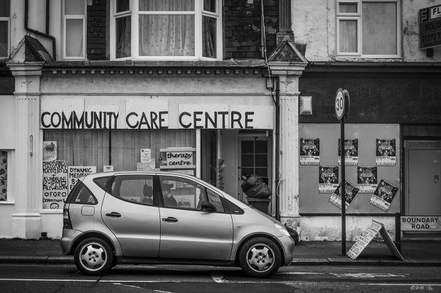 Shop front with hand painted sign saying Community Care Centre and shuttered empty shop with care in foreground. Boundary Road, Portslade On Sea, Sussex UK.  Monochrome Landscape. © P. Maton 2015 eyeteeth.net