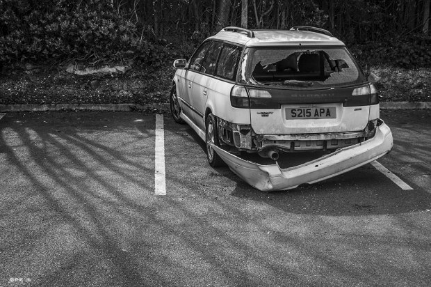 Subaru car with smashed back bumper and window in car park with shadows of trees on asphalt. Lewes, East Sussex UK.  Monochrome Landscape. © P. Maton 2015 eyeteeth.net