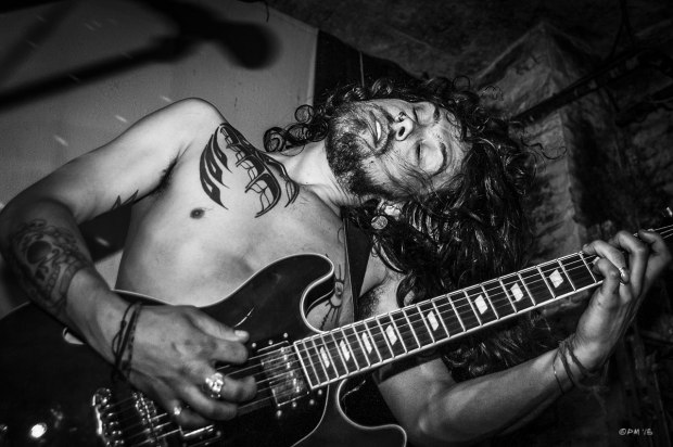 Tattooed topless man with long hair playing guitar. Dominic Knight of the band Dirty White Fever. Monochrome Landscape. © P. Maton 2015 eyeteeth.net