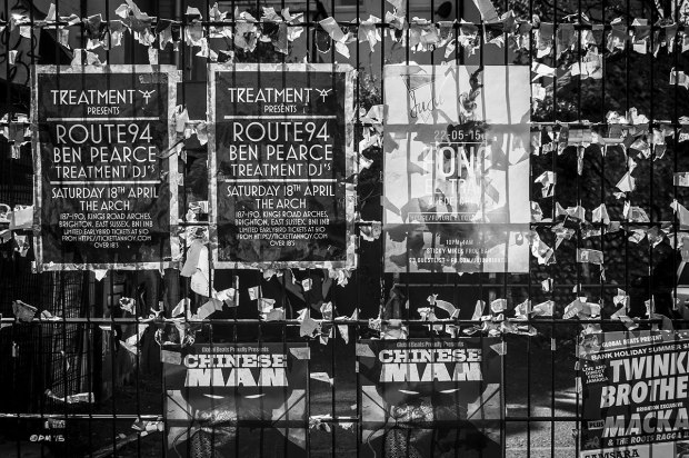 Music posters taped to wire fence with remains of tape backlit by sunlight. Street Photography. North Laine Brighton UK. Monochrome Landscape. © P. Maton 2015 eyeteeth.net