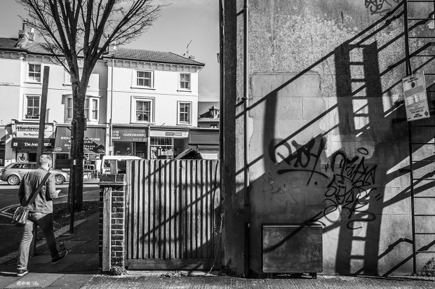 Shadows of fire escape ladder cast across side wall of building with man walking on pavement, Melville Rd with view on to Dyke Rd, Brighton UK. Monochrome Landscape. © P. Maton 2015 eyeteeth.net