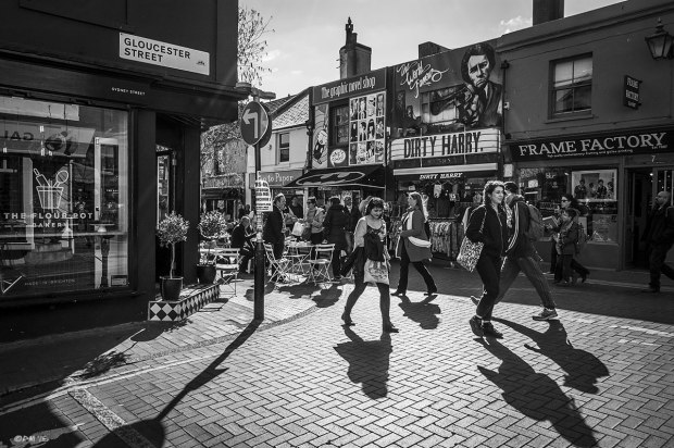 People crossing road in shopping street sunshine with shadows cast toward viewer, street scene with shops: Dirty Harry, The Graphic Novel Shop, Frame Factory and The Flour Pot. Sydney Street North Laine Brighton UK. Monochrome Landscape. © P. Maton 2015 eyeteeth.net