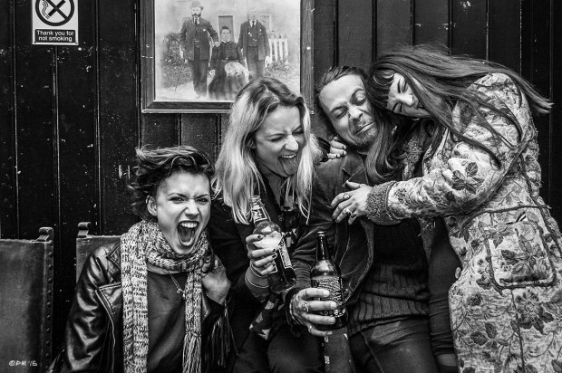Young women and a guy drinking beer and pulling crazy faces  at The Green Door Store in Brighton UK.  Monochrome Landscape. © P. Maton 2015 eyeteeth.net