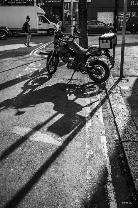 Mororbike casting long shadows on road with girl walking passed. Monochrome Portrait. © 2015 P. Maton eyeteeth.net