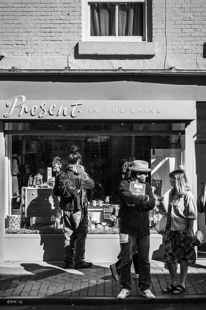Couple talking in sunshine on pavement / sidewalk in front of shop Present In The Laine. Street Scene. Gardner Street North Laine Brighton UK. Monochrome Portrait. © P. Maton 2015 eyeteeth.net