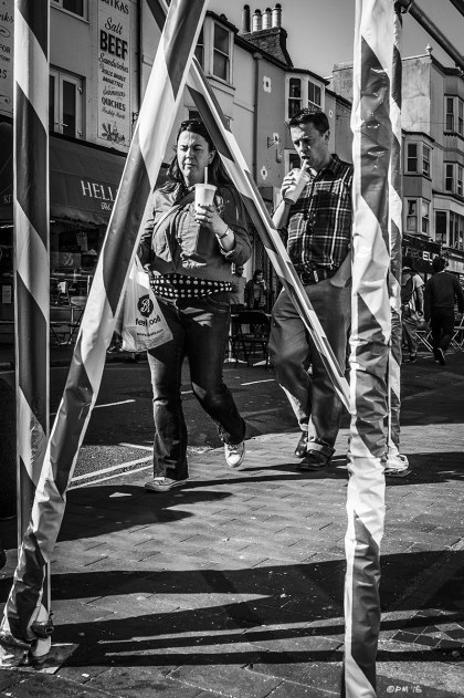 Couple with milkshakes walking in sunshine seen through striped scaffold poles. Street photography. Gardner Street, North Laine Brighton UK. Monochrome Portrait. © P. Maton 2015 eyeteeth.net