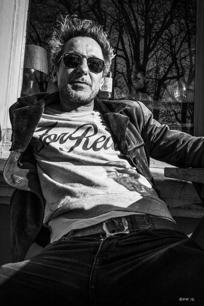 Man with spiky wild hair and shades in For Real teeshirt  suede jacket and jeans sitting in sunshine outside bar. Brighton UK. Monochrome Portrait. © P. Maton 2015 eyeteeth.net