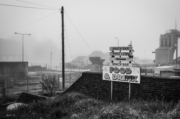 Sign advertising Snack Bar Food and Drink with view over aggregates works and dock lands in fog, Portslade On Sea Sussex UK.  Monochrome Landscape. © P. Maton 2015 eyeteeth.net