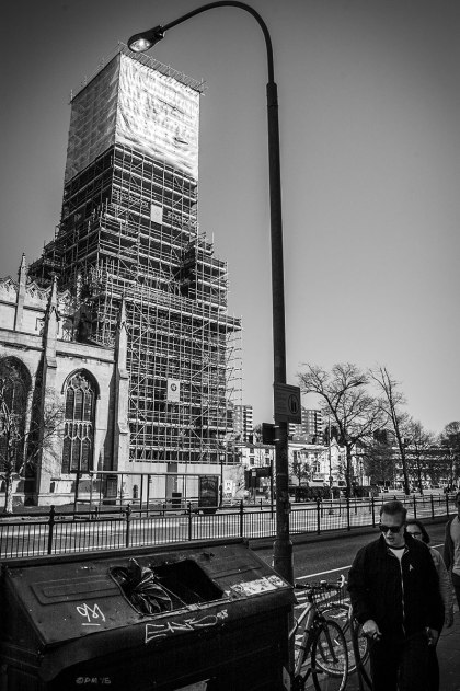Scaffolding over Saint Peters Church tower with lamp post people and dumpster bin in foreground. Brighton UK. Monochrome Portrait. © P. Maton 2015 eyeteeth.net