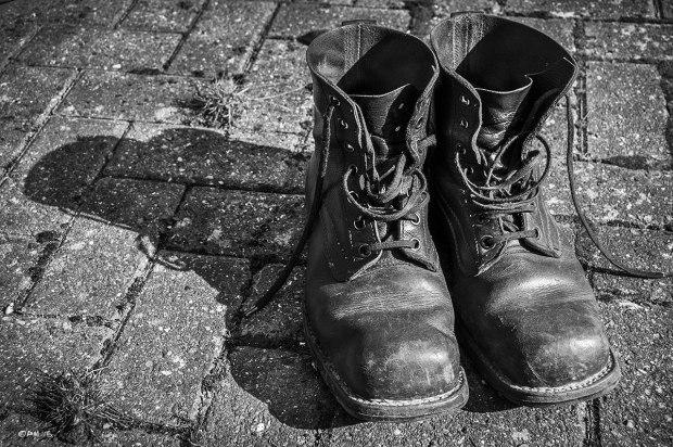 Well worn Swedish Army Boots on brick pavement. Monochrome Landscape. © P. Maton 2015 eyeteeth.net