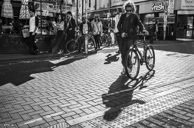 Woman pushing bicycle on road with shadow cast towards viewer by sunshine, shops and people in background street scene. Sydney Street North Laine Brighton UK. Monochrome Landscape. © P. Maton 2015 eyeteeth.net