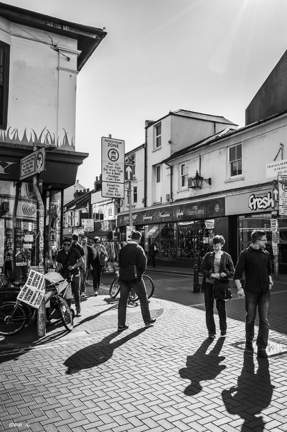 People walking in road with shadows cast towards viewer by sunshine, shops and people in background street scene. Sydney Street North Laine Brighton UK. Monochrome Landscape. © P. Maton 2015 eyeteeth.net
