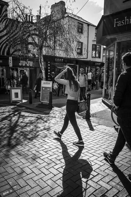 Young woman walking in road being looked at by man with shadows cast towards viewer by sunshine, shops and people in background street scene. Sydney Street North Laine Brighton UK. Monochrome Portrait. © P. Maton 2015 eyeteeth.net