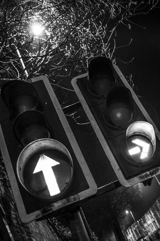 Illuminated arrows on traffic lights at night. Abstract. New Engines Road Brighton UK. Monochrome Portrait. © 2015 P. Maton eyeteeth.net