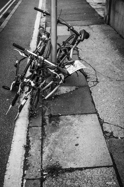Abandoned bicycles attached to signpost on paved sidewalk, Argyle Road Brighton UK. Monochrome Portrait.  © P. Maton 2015 eyeteeth.net