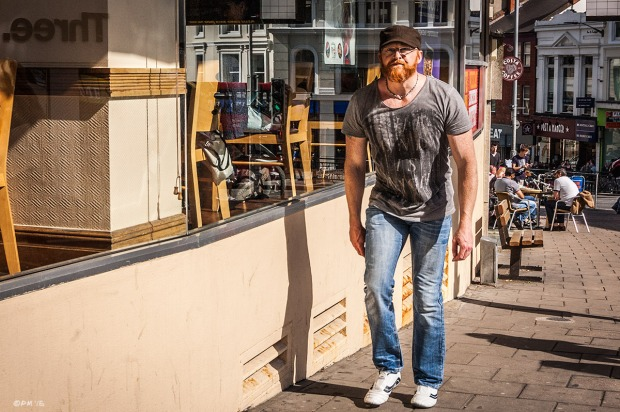 Board shouldered freckled man with red beard, hat and glasses wearing teeshirt and jeans walking next to cafe windows in sunshine. Dyke Road Brighton UK. Colour Landscape. © P. Maton 2015 eyeteeth.net