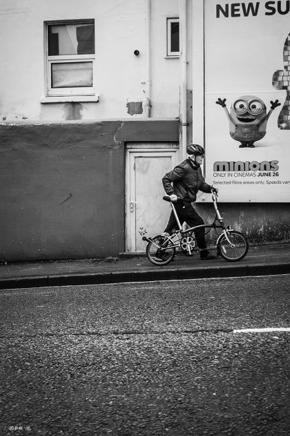 Man pushing bicycle up hill. Old Shoreham Road Brighton UK. Urban Street Photography. Monochrome Portrait. © P. Maton 2015 eyeteeth.net