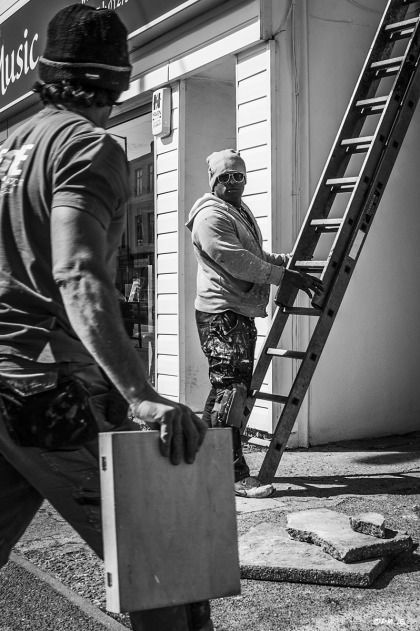 Man in beanie hat and shades holding ladder looking towards camera  as man holding box in foreground looks steps towards him. Workmen, Portland Road Hove UK. Urban Street Monochrome Portrait. ©P. Maton 2015 eyeteeth.net