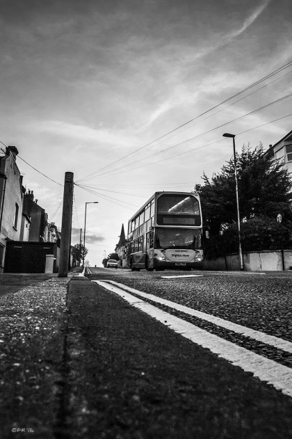 Bus travelling along road towards viewer, low camera angle with strong vanishing point. Old Shoreham Road, Brighton UK. Monochrome Portrait.  © P. Maton 2015 eyeteeth.net