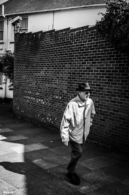 Man in cat with hat and dark glasses walking by wall with security camera CCTV. Newhaven UK. Urban Street Photography.  Monochrome Portrait. © P. Maton 2015