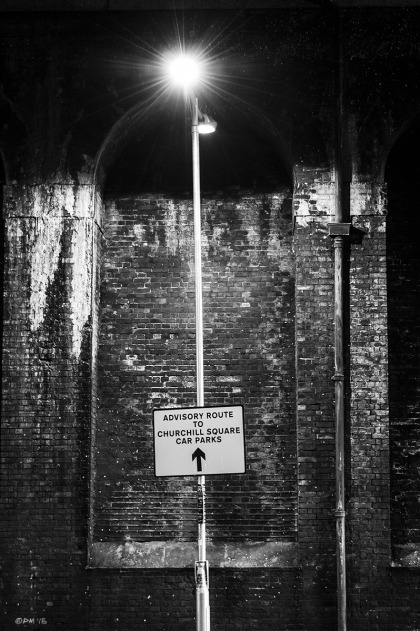 Advisory Route sign with arrow pointing upwards to street lamp with victorian viaduct wall in background. New England Road Brighton UK. Monochrome Portrait.  © P. Maton 2015 eyeteeth.net