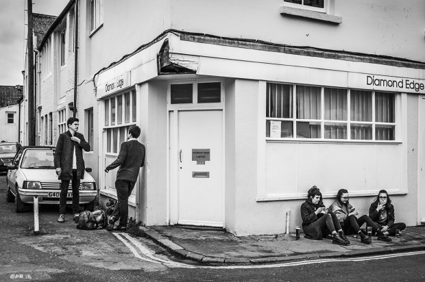 Two young me standing on street corner by three young women sitting on pavement smoking. Gloucester Road Brighton UK.  Monochrome Landscape. © P. Maton 2015 eyeteeth.net