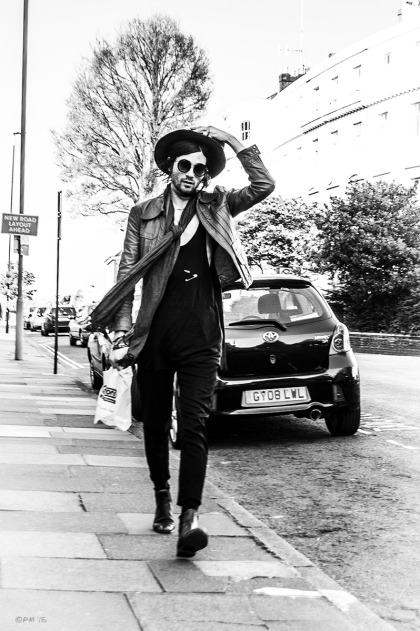 Handsome man dressed in hipster fashion adjusting his hat while walking down the street towards camera. Fashion, street photography. Monochrome portrait. Vernon Terrace Brighton UK. © P. Maton 2105 eyeteeth.net