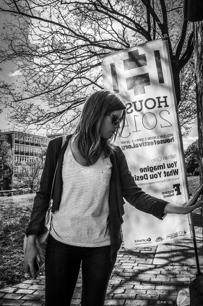 Woman touching wall by House 2015 sign with tree in background casting shadows towards camera. St Nicholas Church Brighton UK. Brighton House Festival, Brighton Festival. Monochrome Portrait. © P. Maton 2015 eyeteeth.net