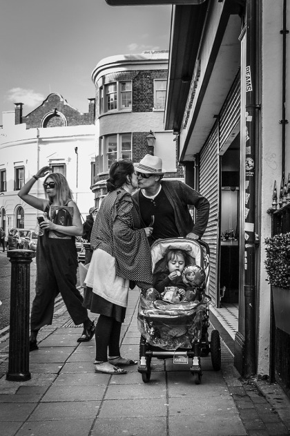 Couple with pram kissing in street while child looks at a potato chip / crisp with woman raising her arm in background. Ship Street Brighton UK. Ship Street Brighton UK. Street Photography. Monochrome Portrait. © P. Maton 2015 eyeteeth.net