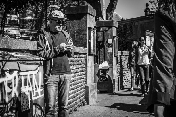 Man texting on mobile phone standing by wall as people pass by on pavement. Ship Street Brighton UK. Ship Street Brighton UK. Street Photography. Monochrome Portrait. © P. Maton 2015 eyeteeth.net