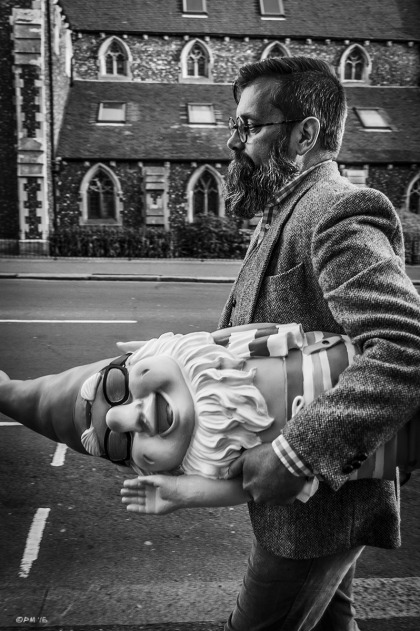 Man with beard and glasses dressed in Tweed carrying plastic gnome under his arm walking in street with church in background. Street photography. Church Road Hove UK. Monochrome Portrait. © P. Maton 2015 eyeteeth.net