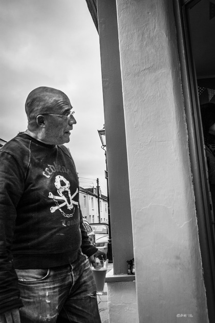 Man with pint of beer in hand looking into doorway. Trafalgar Street Brighton UK. Gloucester Road Brighton UK.Urban Street Photography. Monochrome Portrait. © P. Maton 2015 eyeteeth.net