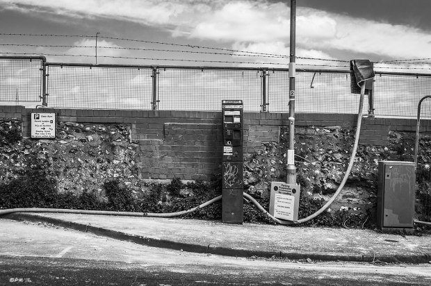 Parking ticket machine by wall with mesh fencing and pipe on Howard Place Brighton UK.  Urban Street photography. Monochrome Landscape. P. Maton 2015 eyeteeth.net