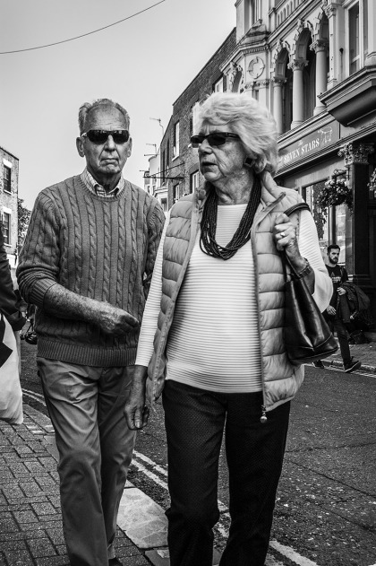 Senior couple in shades walking along street. Ship Street Brighton UK. Ship Street Brighton UK. Street Photography. Monochrome Portrait. © P. Maton 2015 eyeteeth.net