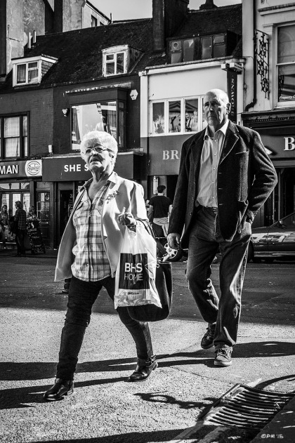 Elderly couple walking down street in sunshine. Ship Street Brighton UK. Street Photography. Monochrome Portrait. © P. Maton 2015 eyeteeth.net