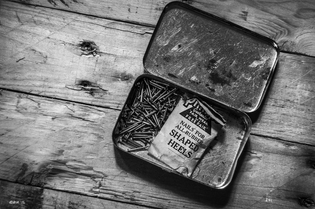 Open tin with old vintage paper packet of  shoe heel nails on rough wooden surface. Monochrome Landscape  © P. Maton 2015 eyeteeth.net