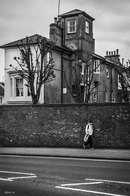 Young and with skateboard walking beside brick wall with weathered building in background. New England Road Brighton UK. Urban Street Photography. Monochrome Portrait. © P. Maton 2015 eyeteeth.net