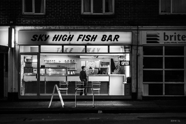 Boy standing at counter of Sky High Fish Bar at night with illuminated sign. Portland Road Hove UK. Urban Street Photography. Monochrome Landscape. © P. Maton 2015 eyeteeth.net