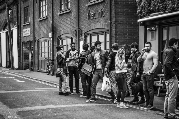 People gathered drinking and smoking outside The Eagle pub with man glancing down at young woman bottom as he leaves. Gloucester Road Brighton UK.Urban Street Photography. Monochrome Landscapet. © P. Maton 2015 eyeteeth.net