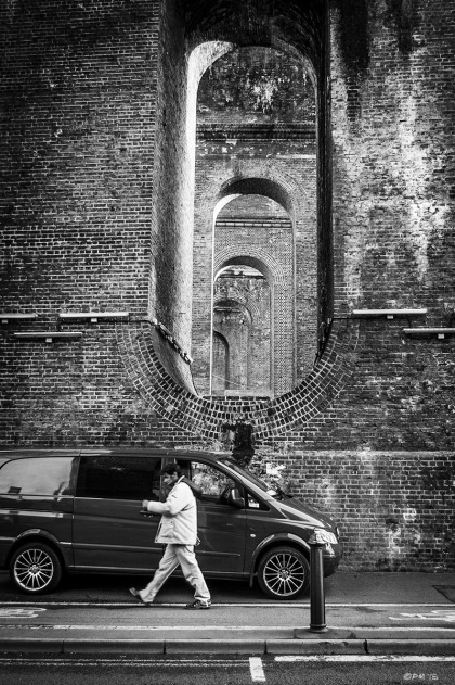Man walking next to parked van with Victorian brick viaduct looming overhead. Preston Road Brighton UK. Industrial Monochrome Portrait. © P. Maton 2015 eyeteeth.net