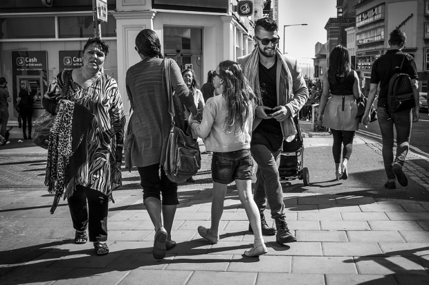 Middle aged woman with apprehensive expression and smiling hipster male passing mother and child with couple holding hands in background, sunshine and shadows cast. West Street Brighton. Monochrome Landscape. © P. Maton 2015 eyeteeth.net