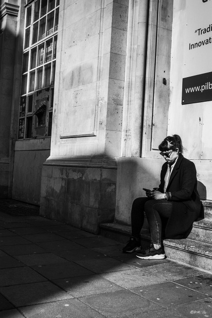 Woman texting on phone sitting on steps with shadow looming over her. Ship Street Brighton UK. Ship Street Brighton UK. Street Photography. Monochrome Portrait. © P. Maton 2015 eyeteeth.net