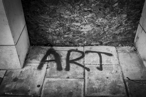 The word ART sprayed on paving slabs by chip board shuttering in doorway. Urban Abstract Photography. London Road Brighton UK.  Monochrome Landscape. © P. Maton 2015 eyeteeth.net