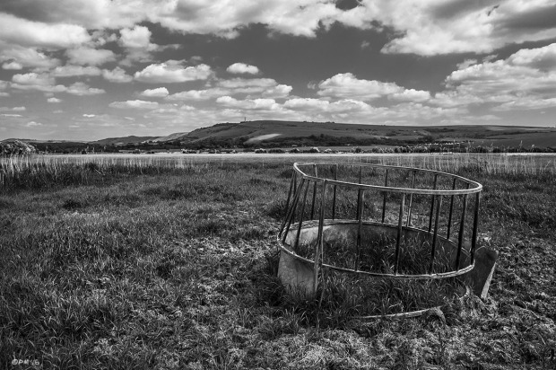 Round metal Cattle Feeder in field with view to Truleigh Hill on South Downs in distance. Seven Sister Country Park, West Sussex UK. Monochrome Landscape. © P. Maton 2014 eyeteeth.net