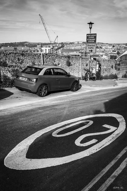 Road marking '20' in foreground with parked car and view across Brighton with diversion sign and crane. Howard Place, Brighton UK. Urban Street Photography.  Monochrome Portrait. © P. Maton 2015 eyeteeth.net