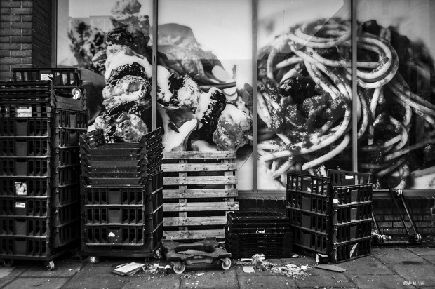Food containers stacked on pavement sidewalk, in front of giant food photographs in shop window. Dyke Road Brighton UK. Monochrome Urban Landscape. © P. Maton 2015 eyeteeth.net