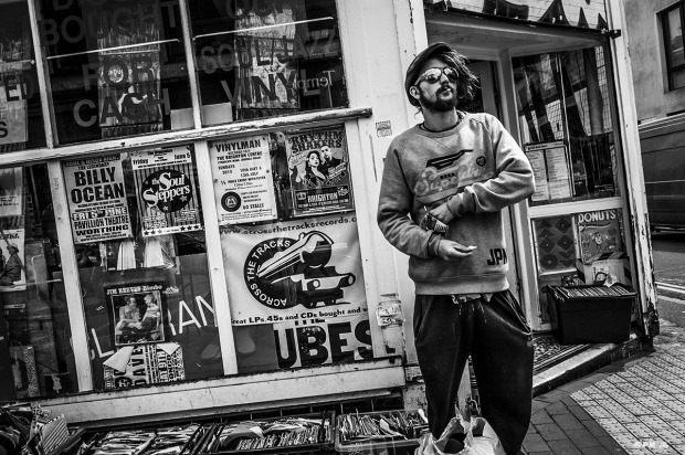 Guy in mirror shades and Superdry sweat shirt standing rolling a cigarette outside Across The Tracks record store, Sydney Street Brighton Sussex UK. Monochrome Landscape. © P. Maton 2015 eyeteeth.net