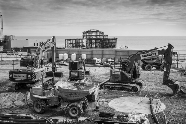Heavy plant vehicles parked in construction site of i360 tower with West Pier ruins and sea in background, Brighton UK. Monochrome Landscape. © P. Maton 2015 eyeteeth.net