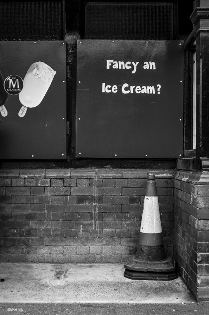 Kiosk panel with the words 'Fancy an Ice Cream?'  above traffic cone. Western Esplanade Hove UK. Monochrome Portrait. © P. Maton 2015 eyeteeth.net