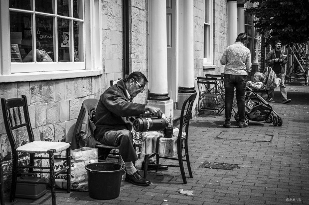 Man sitting using chair as table and pouring hot drink from flask in front of old building near cafe on High Street in Lewes East Sussex. Monochrome Landscape. © P. Maton 2015 eyeteeth.net
